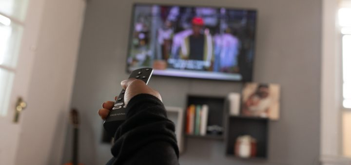 black hand holding a television remote